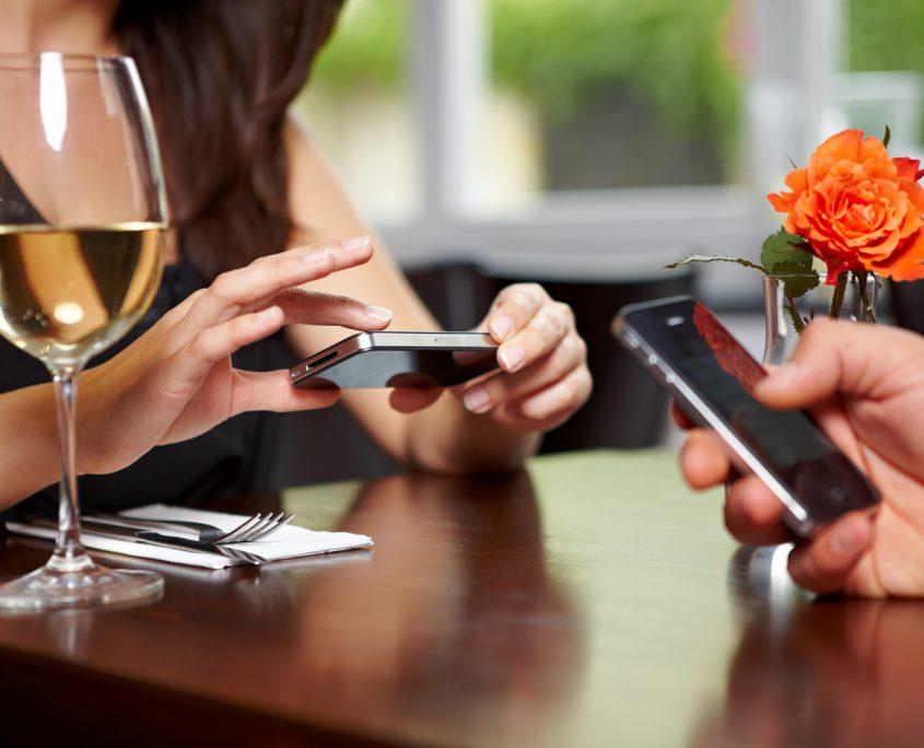 Hände sind mit Handys beschäftigt im Restaurant